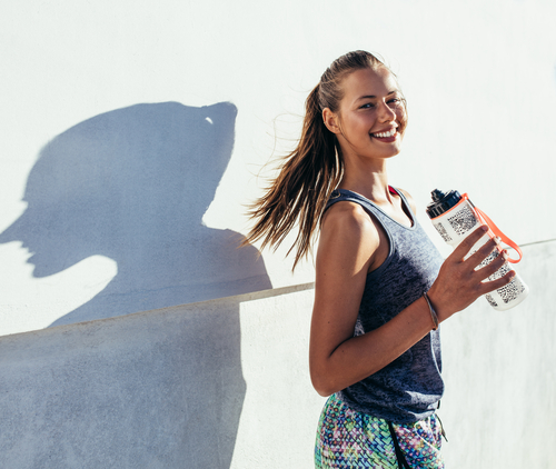 Woman holding water bottle after run