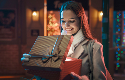 A smiling woman opening a glowing gift box