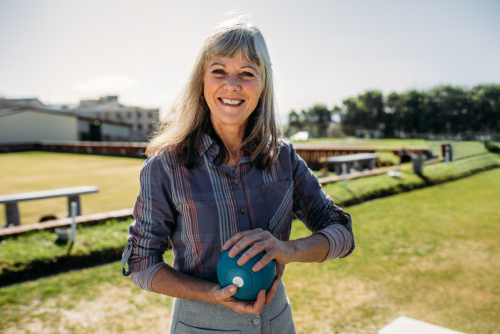 A woman smiling and holding a spherical object
