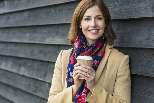 woman tan jacket and floral scarf holding a cup of coffee